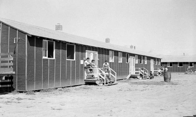 FILE - In this file photo taken Sept. 21, 1942, relocated Japanese-Americans sit on small front porches on barracks at Rohwer Relocation Center near Rohwer, Ark. The National Park Service on Thursday, June 12, 2014, awarded nearly a quarter-million dollars in grants to projects in Arkansas that help preserve and interpret sites that were used to confine Japanese Americans during World War II. (AP Photo/Horace Cort, File)