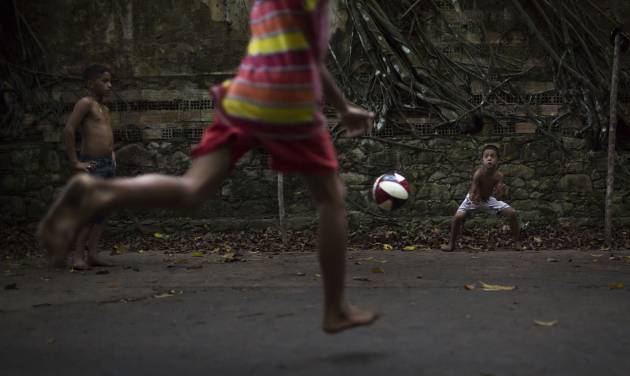 In this May 21, 2014 photo, A boy kicks a penalty during a soccer match in the ruins of Paricatuba, near Manaus, Brazil. Children of the tiny village of Paricatuba, which grew up around the villa, use the ruins as a spot for energetic games of barefoot soccer or to scare themselves silly. Teenagers come here to make out, and older people to get drunk. (AP Photo/Felipe Dana)