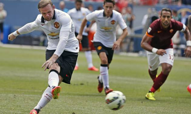 Manchester United's Wayne Rooney, left, kicks for a goal during the first half of an exhibition soccer match against AS Roma at Mile High Stadium, in Denver, Saturday, July 26, 2014. (AP Photo/Brennan Linsley)
