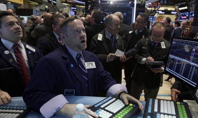 FILE - In this Wednesday, Jan. 8, 2014, file photo, specialist Michael Shearin, foreground center, works at his post on the floor of the New York Stock Exchange. U.S. stock futures are rising, Thursday, Jan. 9, 2014, ahead of the opening bell on Wall Street, helped by a report that the number of people who filed for unemployment benefits last week fell more than expected. (AP Photo/Richard Drew, File)