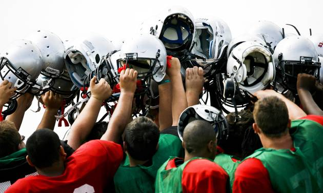 U.S. Grant players hold their helmets up after a 2011 scrimmage at U.S. Grant High School. Photo by Zach Gray, The Oklahoman Archives