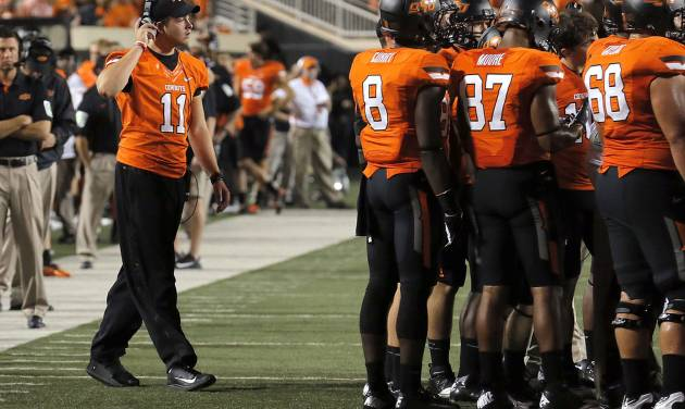 Oklahoma State's Wes Lunt (11) walks to the OSU huddle during a college football game between Oklahoma State University (OSU) and the University of Texas (UT) at Boone Pickens Stadium in Stillwater, Okla., Saturday, Sept. 29, 2012. Photo by Sarah Phipps, The Oklahoman