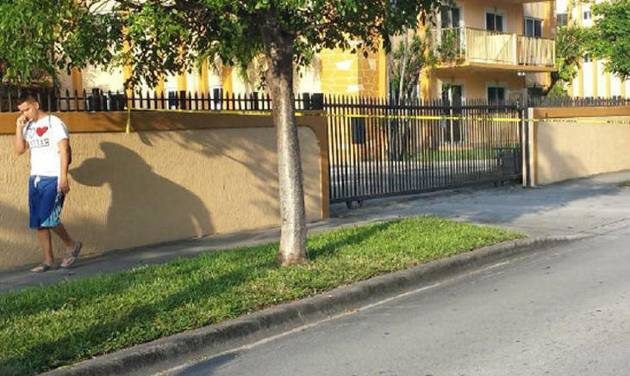 A resident of an apartment building where seven people were killed walks by police tape in Hialeah, Fla., early Saturday, July 27, 2013. A gunman holding hostages inside the apartment complex killed six people before being shot to death by a SWAT team that stormed the building early Saturday following an hours-long standoff, police said. (AP Photo/The Miami Herald, Benjamin S. Brasch)