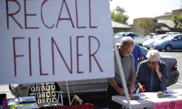 Greg Timms, left, signs a petition to recall San Diego Mayor Bob Filner, alongside Tana Piontek, right, at a stand set up in the parking lot of a shopping center Wednesday, Aug. 21, 2013, in San Diego.  Pressure is mounting against San Diego's mayor to resign after a sexual harassment lawsuit was filed against him, and the Democratic National Committee plans to vote on a resolution Friday urging him to step down immediately. (AP Photo/Gregory Bull)