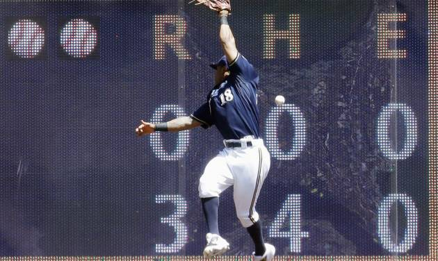 Milwaukee Brewers left fielder Khris Davis can't catch a ball hit by Colorado Rockies' Brandon Barnes during the second inning of a baseball game Sunday, June 29, 2014, in Milwaukee. (AP Photo/Morry Gash)
