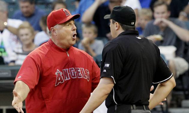 Los Angeles Angels manager Mike Scioscia, left, argues with home plate umpire Lance Barrett during the first inning of a baseball game against the Chicago White Sox in Chicago, Friday, Aug. 3, 2012. (AP Photo/Nam Y. Huh)