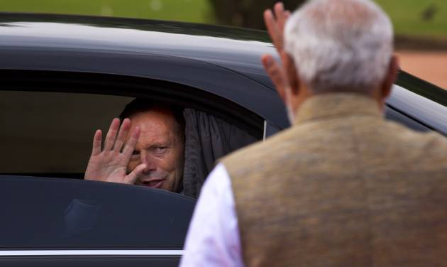 Australian Prime Minister Tony Abbott, left, waves at his Indian counterpart Narendra Modi as he leaves after a ceremonial welcome in New Delhi, India, Friday, Sept. 5, 2014. Abbott is on a two-day visit to India. (AP Photo/Saurabh Das)