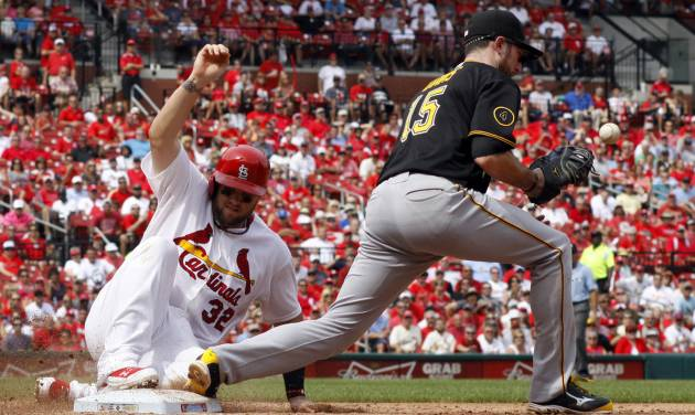 St. Louis Cardinals' Matt Adams, left, slides safely back to first as Pittsburgh Pirates first baseman Ike Davis bobbles the throw after Cardinals' Jhonny Peralta lined out during the sixth inning of a baseball game Wednesday, Sept. 3, 2014, in St. Louis. The Cardinals won 1-0. (AP Photo/Jeff Roberson)