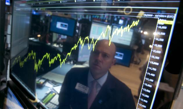 Specialist Jay Woods is reflected in a screen at his post that shows five years of the Dow Jones industrial average, on the floor of the New York Stock Exchange, Thursday, July 3, 2014. The Dow Jones industrial average jumped above 17,000 for the first time Thursday after the government reported a surge in hiring last month that was much bigger than investors and economists were expecting. (AP Photo/Richard Drew)