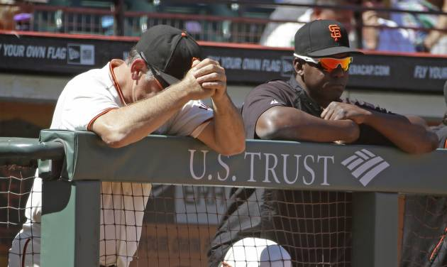San Francisco Giants manager Bruce Bochy, left, and hitting coach Hensley Meulens, right, rest on the dugout railing in the ninth inning of their baseball game against the St. Louis Cardinals, Thursday, July 3, 2014, in San Francisco. St. Louis won the game 7-2. (AP Photo/Eric Risberg)
