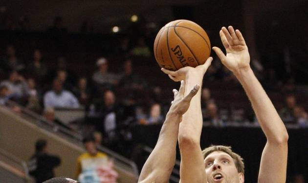Dallas Mavericks' Dirk Nowitzki, right, of Germany shoots while being guarded by Philadelphia 76ers' Thaddeus Young, left, during the first half of an NBA basketball game, Friday, Feb. 21, 2014, in Philadelphia. (AP Photo/Chris Szagola)