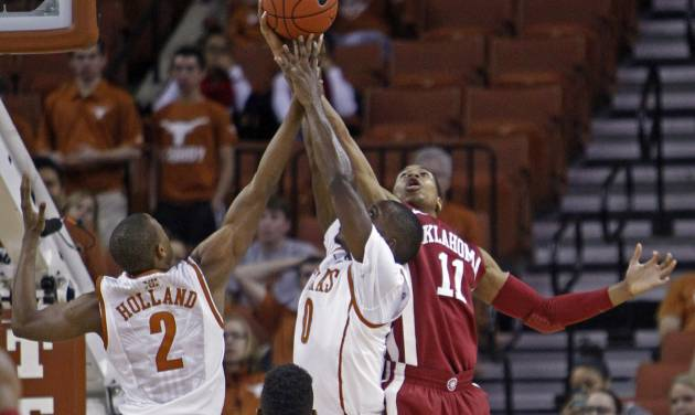 Oklahoma guard Isaiah Cousins (11) comes down with a rebound against Texas guard Kendal Yancy (0) and Demarcus Holland (2) during the first half of an NCAA college basketball game Saturday, Jan. 4, 2014, in Austin, Texas. (AP Photo/Michael Thomas)