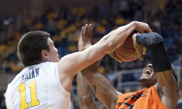 West Virginia's Nathan Adrian, left, blocks Oklahoma State's Le'Bryan Nash during the second half of an NCAA college basketball game Saturday, Jan. 11, 2014, in Morgantown, W.Va. Oklahoma State won 73-72. (AP Photo/Andrew Ferguson)
