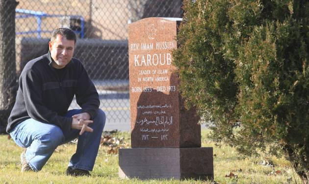 ADVANCE FOR USE SUNDAY, DEC. 30, 2012 AND THEREAFTER - This Dec. 18, 2012 photo shows Detroit Associated Press reporter Jeff Karoub next to the tombstone of his grandfather, The Rev. Imam Hussien Karoub, in Berkley, Mich. Wanting to fill some ancestral gaps, Jeff is piecing together the story of his grandfather who immigrated to America in 1912. (AP Photo/Carlos Osorio)