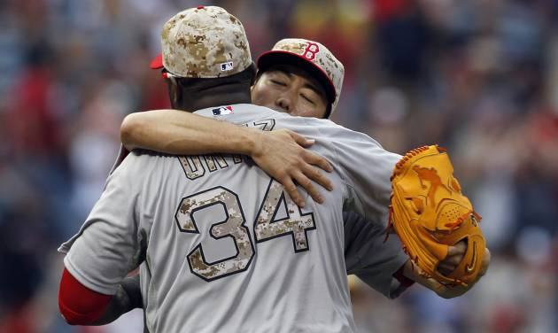 Boston Red Sox pitcher, Koji Uehara (19) hugs David Ortiz (34) after they defeated the Atlanta Braves 8-6 in the ninth inning of a baseball game on Monday, May 26, 2014, in Atlanta, Ga. (AP Photo/Butch Dill)