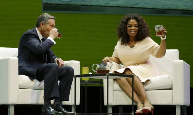 Howard Schultz, left, chairman and CEO of Starbucks Coffee Company, sits and drinks tea with Oprah Winfrey, right, to announce their partnership to offer Teavana Oprah Chai tea, Wednesday, March 19, 2014, at Starbucks' annual shareholders meeting in Seattle. (AP Photo/Ted S. Warren)