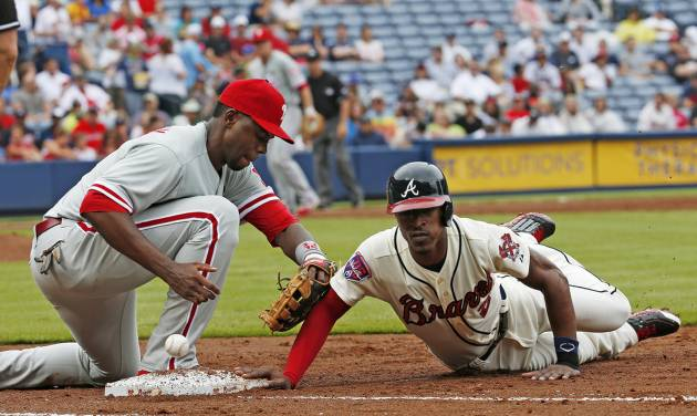 Atlanta Braves' B.J. Upton (2) dives back to first base as the ball gets away from Philadelphia Phillies first baseman John Mayberry Jr. (15) in the third inning of a baseball game  in Atlanta, Sunday, July 20, 2014. Upton advanced to second on the play. (AP Photo/John Bazemore)