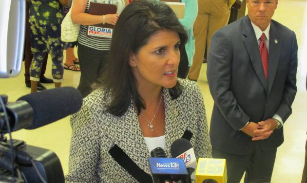 South Carolina Gov. Nikki Haley listens to a question while meeting with reporters in Atlantic Beach, S.C., on Tuesday, July 29, 2014. The governor had just urged town council to work with her to end the Atlantic Beach Bikefest following violence in the Myrtle Beach area last Memorial Day. She said the state is willing to work to help redevelop the community to make it a family-friendly tourist destination. To Haley's left is Duane Parrish, the director of the South Carolina Department of Parks, Recreation and Tourism.  (AP Photo/Bruce Smith)