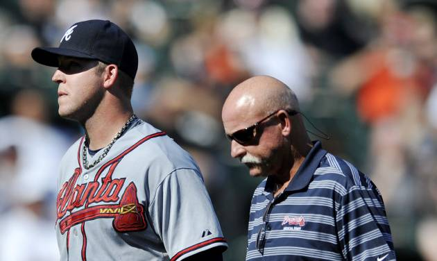 Atlanta Braves starting pitcher Paul Maholm left, walks to the dugout with a trainer after being pulled during the fourth inning of an interleague baseball game against the Chicago White Sox in Chicago, Saturday, July 20, 2013. (AP Photo/Paul Beaty)