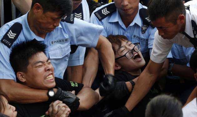 Protesters are taken away by police officers after hundreds of protesters staged a peaceful sit-ins overnight on a street in the financial district in Hong Kong Wednesday, July 2, 2014, following a huge rally to show their support for democratic reform and oppose Beijing's desire to have the final say on candidates for the chief executive's job. (AP Photo/Kin Cheung)