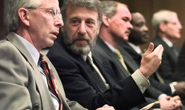 "FILE - In this Thursday, May 6, 1999 file photo, George Zimmer, second from left, gestures to Andy Dolich prior to a meeting, in Oakland, Calif. On Tuesday, June 25, 2013, Men's Wearhouse Inc., offered some details on why it parted ways with founder Zimmer, saying that Zimmer seemed to have difficulty ""accepting the fact that Men's Wearhouse is a public company with an independent board of directors and that he has not been the chief executive officer for two years.""(AP Photo/Ben Margot, File)"