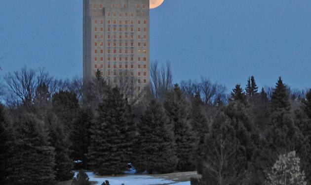 In this photo taken Wednesday, March 26, 2013, Bismarck, N.D., the full Lenten moon rises from behind the North Dakota capitol in Bismarck, N.D. Early settlers called the last full moon of winter the Lenten moon due to its arrival just before Easter. (AP Photo/The Bismarck Tribune, Tom Stromme)