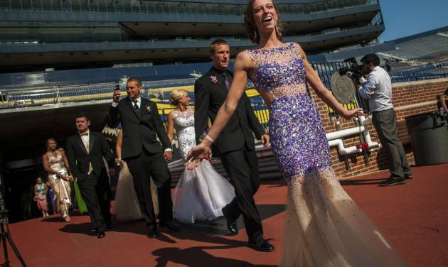 Durand High School students smile as they enter onto the field at Michigan Stadium on the University of Michigan campus, Saturday, May 10, 2014, in Ann Arbor, Mich. The junior-senior prom for students at Durand High School was the first prom hosted by the 100,000-plus-seat football venue. The group took photos on the field, visited the locker rooms and had their dancing and dinner in the Jack Roth Stadium Club until midnight. (AP Photo/The Flint Journal, Jake May) LOCAL TV OUT; LOCAL INTERNET OUT