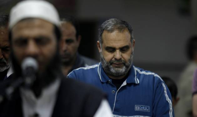 """In this Monday, June 24, 2013 photo, Mohammed Rantisi, 55, prays al Fajr """"early morning"""" prayer behind the Imam at a mosque in Gaza City. On the day of his induction, Baraa, Mohammed's son, was told to wait near a mosque. A white car drove up. Secret passwords were exchanged. And then he was sworn into the Muslim Brotherhood, an exclusive movement that sees itself on a divine mission to establish Islamic rule. AP reporters got rare access to the Rantisi family, the closest thing to a royal clan in the Brotherhood in Gaza, at a time when the movement is under siege throughout the region. (AP Photo/Hatem Moussa)"""