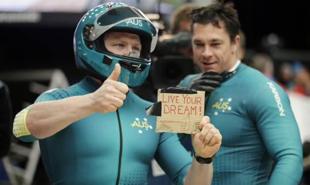 "The team from Australia AUS-1, piloted by Heath Spence and brakeman Duncan Harvey, hold up a sign that says ""Live Your Dream,"" after their third run during the men's two-man bobsled competition at the 2014 Winter Olympics, Monday, Feb. 17, 2014, in Krasnaya Polyana, Russia. (AP Photo/Jae C. Hong)"