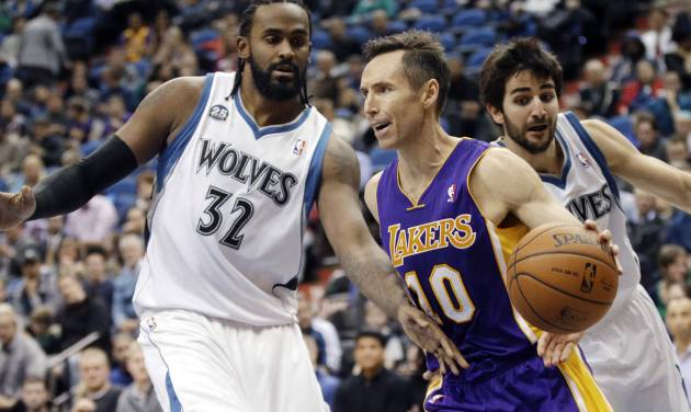 Los Angeles Lakers' Steve Nash, center, drives as Minnesota Timberwolves' Ronny Turiaf, left, of France, and Ricky Rubio, of Spain, defend during the second half of an NBA basketball game, Tuesday, Feb. 4, 2014, in Minneapolis. The Timberwolves won 109-99. Nash had been sidelined since Nov. 10 because of nerve problems in his back. (AP Photo/Jim Mone)
