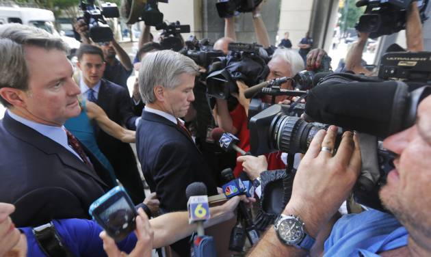 Former Virginia Gov. Bob McDonnell, center, tries to move through the throng of media as he and his attorney, John Brownlee,  left, arrive at federal court in Richmond, Va., Tuesday, Aug. 19, 2014. McDonnell is presenting the second day of his defense on corruption charges. (AP Photo/Steve Helber)