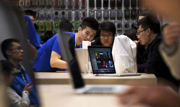 FILE - In this Saturday, Oct. 20, 2012, file photo, an Apple staff introduces a Macbook Pro computer to a customer at a newly-opened Apple Store in Wangfujing shopping district in Beijing. Apple Inc.'s MacBook Pro, high-resolution, 13-inch version starts at $1,299. I  (AP Photo/Andy Wong)