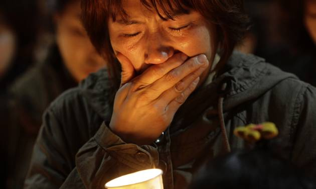 A woman offers prayers during a candlelight vigil for the missing passengers of a sunken ferry at Danwon High School in Ansan, South Korea, Thursday, April 17, 2014. An immediate evacuation order was not issued for the ferry that sank off South Korea's southern coast, likely with scores of people trapped inside, because officers on the bridge were trying to stabilize the vessel after it started to list amid confusion and chaos, a crew member said Thursday.  (AP Photo/Wonghae Cho)