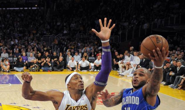 Orlando Magic guard Jameer Nelson, right, puts up a shot as Los Angeles Lakers center Dwight Howard defends during the first half of their NBA basketball game, Sunday, Dec. 2, 2012, in Los Angeles. (AP Photo/Mark J. Terrill)