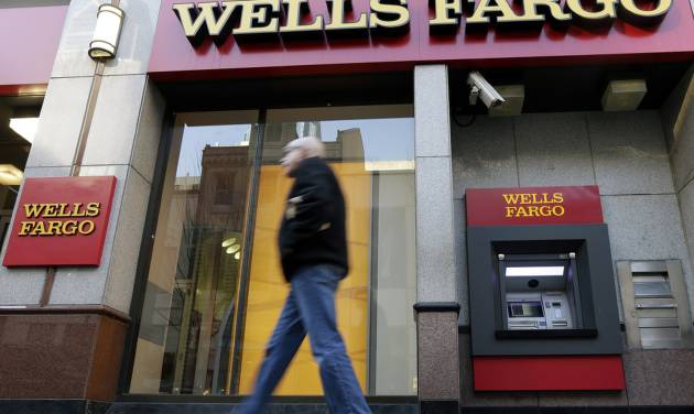 FILE - In this Wednesday, Dec. 19, 2012, file photo, a man walks past a Wells Fargo location in Philadelphia. Wells Fargo reports quarterly financial results on Friday, July 11, 2014. (AP Photo/Matt Rourke, File)