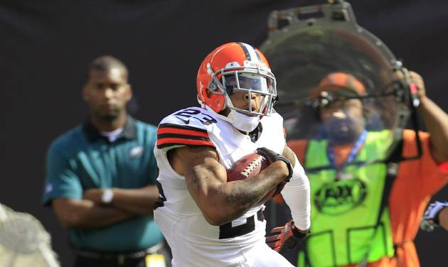 Cleveland Browns defensive back Joe Haden (23) is tackled by Philadelphia Eagles quarterback Michael Vick (7) after intercepting the ball in the third quarter of an NFL football game on Sunday, Sept. 9, 2012, in Cleveland. (AP Photo/Tony Dejak)