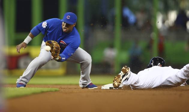 Miami Marlins' Jake Marisnick, right, steals second on a late throw from the Chicago Cubs catcher to second baseman Luis Valbuena, left, during the first inning of a baseball game in Miami, Monday, June 16, 2014. (AP Photo/J Pat Carter)
