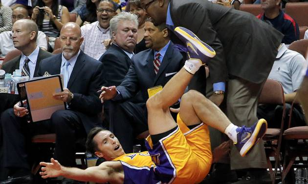 Los Angeles Lakers' Steve Nash, bottom, collides with head coach Mike Brown as he goes after a loose ball during the first half of an NBA preseason basketball game against the Utah Jazz in Anaheim, Calif., Tuesday, Oct. 16, 2012. (AP Photo/Jae Hong)