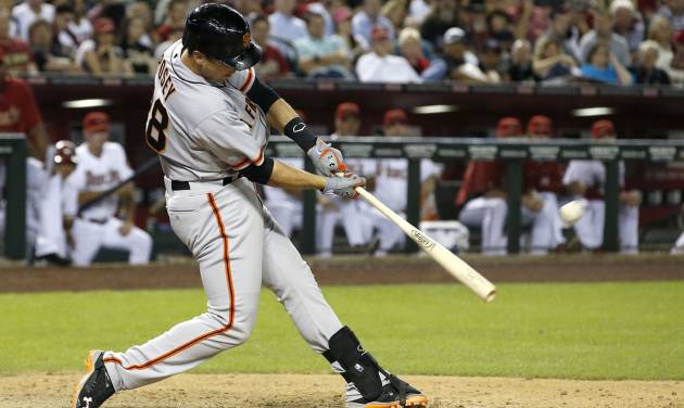 San Francisco Giants' Buster Posey connects for a 2-run home run against the Arizona Diamondbacks during the ninth inning of an opening day baseball game, Monday, March 31, 2014, in Phoenix. (AP Photo/Ross D. Franklin)