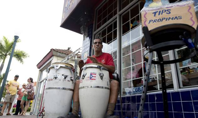 This April 30, 2014 photo shows Pablo Gonzalez Portilla playing Latin music on his drums outside a Cuban gift shop along Calle Ocho (Eighth Street) in Miami's Little Havana. Once a refuge for Cuban exiles rekindling the tastes and sounds a lost home, today Miami's Little Havana is a mosaic of cultures and a popular tourist destination. (AP Photo/J Pat Carter)