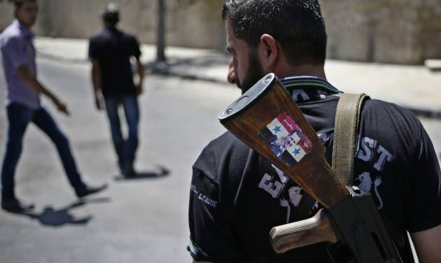 """FILE - This Aug. 21, 2013 file photo shows a Syrian military soldier holding his AK-47 with a sticker of Syrian President Bashar Assad and Arabic that reads, """"Syria is fine,"""" as he stands guard at a check point in Damascus, Syria. President Barack Obama is asking Congress for $500 million to train and arm vetted members of the Syrian opposition, as the U.S. grapples for a way to stem a civil war that has also fueled the al-Qaida inspired insurgency in neighboring Iraq.  (AP Photo/Hassan Ammar, File)"""