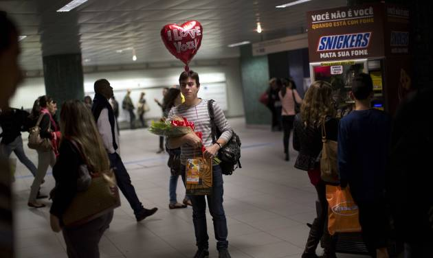 Bearing gifts, Junio waits for his boyfriend Lenon in Sao Paulo's metro, Brazil, Wednesday, June 11, 2014. A threatened second round of a subway strike in Sao Paulo would cripple transportation in South America's biggest city. Authorities are counting on the subway to carry most fans to Sao Paulo games. (AP Photo/Rodrigo Abd)