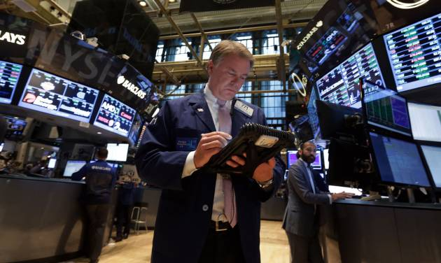 FILE - In this Sept. 18, 2013 file photo, Trader F. Hill Creekmore works on the floor of the New York Stock Exchange. Global stock markets fell Friday Sept. 20, 2013, two days after the Fed announced it would keep its unprecedented stimulus in place. Public holidays kept trading muted in Asia. (AP Photo/Richard Drew, File)