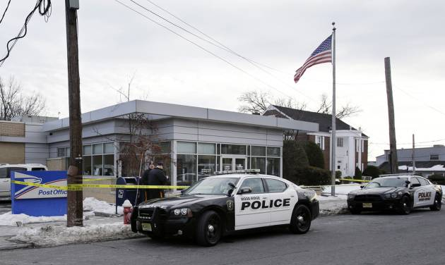 Police officers stand guard outside the closed post office in Wood-Ridge, N.J., Friday, Jan. 31, 2014. The FBI says a powder mailed to several locations in New York and New Jersey, including at least five hotels near the site of Sunday's Super Bowl appears not to be dangerous. (AP Photo/Mel Evans)