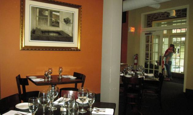 This May 28, 2014 photo shows the dining room at Antica, a restaurant in Chadds Ford, Pa. The restaurant is located near the Brandywine River Museum, which has an extensive collection of artwork by the Wyeth family and offers tours of nearby homes and studios where N.C. Wyeth, his son Andrew Wyeth and grandson Jamie Wyeth lived and worked. The restaurant is decorated with prints of Wyeth artwork. (AP Photo/Beth J. Harpaz)