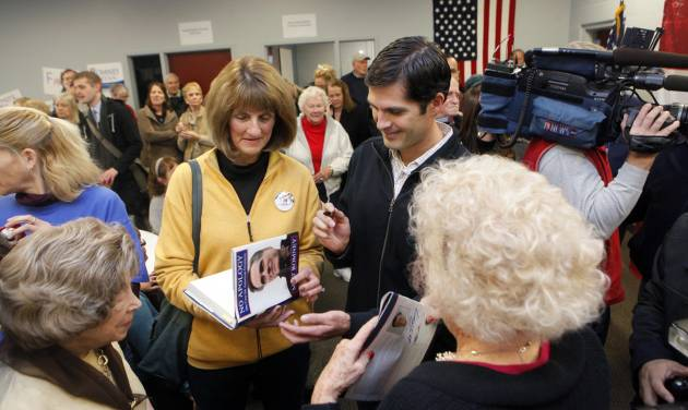 Matt Romney signs a book about his dad, Mitt Romney, for Nancy Eardley of Cascade Township on Monday, Nov. 5, at the Kent County Republican Headquarters. Grand Rapids was the first of several Michigan stops for Matt and his brother Josh. (AP Photo/The Grand Rapids Press, Emily Zoldaz) ALL LOCAL TV OUT; LOCAL TV INTERNET OUT
