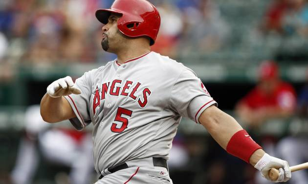 Los Angeles Angels' Albert Pujols follows through on his solo home run against the Texas Rangers during the first inning of a baseball game, Saturday, Aug. 16, 2014, in Arlington, Texas. (AP Photo/Jim Cowsert)