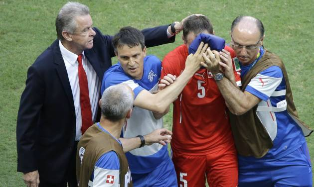Switzerland's coach Ottmar Hitzfeld, left, comforts his injured player Steve von Bergen, second right, during the group E World Cup soccer match between Switzerland and France at the Arena Fonte Nova in Salvador, Brazil, Friday, June 20, 2014. (AP Photo/Sergei Grits)