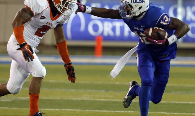 Tulsa's Jordan James looks for room as UTEP's (2) DeShawn Grayson pursues during first half of an NCAA college football game in Tulsa, Okla., Thursday Oct 11, 2012. (AP Photo/Tulsa World, Tom Gilbert)