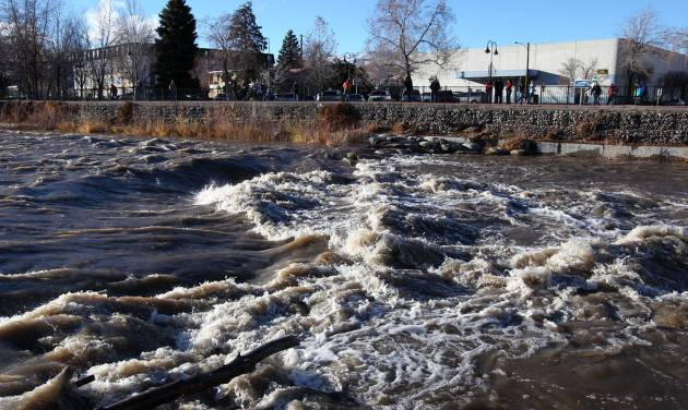 People come out to watch the surging Truckee River, in downtown Reno, Nev., on Sunday, Dec. 2, 2012, as a heavy, wet storm hit the Northern Nevada region. The storm delivered more snow and less rain than forecast, blunting the flood danger. (AP Photo/Cathleen Allison)